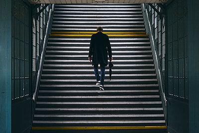 Man walking in a subway station - p1696m2294454 by Alexander Schönberg