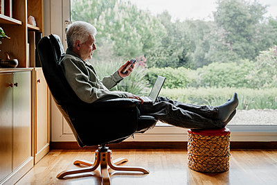 Senior man using mobile phone while sitting on chair at home - p300m2281368 by VITTA GALLERY