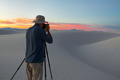 Caucasian man photographing desert at sunset - p555m1523060 by Marc Romanelli