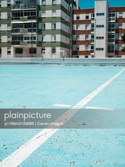 Close up of blue court lines against colorful buildings - p1166m2129985 by Cavan Images