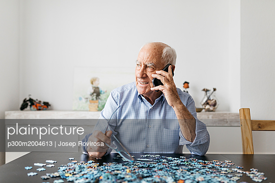 Happy senior man using smartphone while doing a puzzle at home - p300m2004613 von Josep Rovirosa
