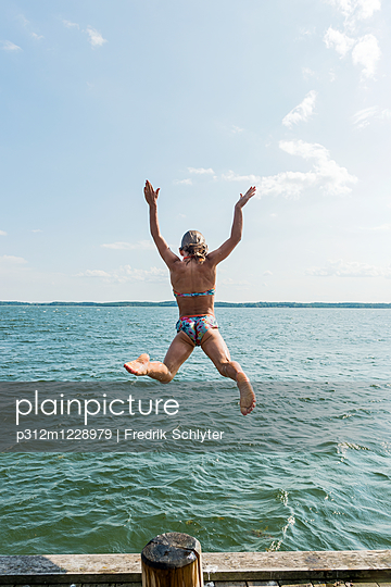 Woman jumping into sea - p312m1228979 by Fredrik Schlyter