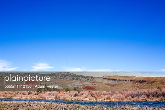 Creek near hills in desert landscape under blue sky, Painted Hills, Oregon, United States - p555m1412150 by Adam Hester