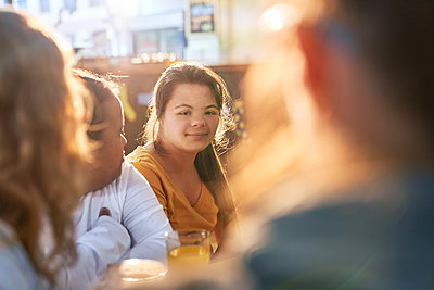 Portrait smiling young woman with Down Syndrome in cafe with friends - p1023m2161831 by Trevor Adeline