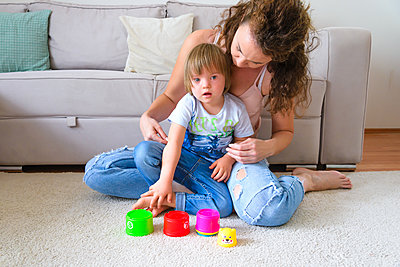 Single mother is playing with her disabled child in their appart - p1166m2247193 by Cavan Images