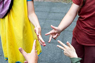 Four children play in Rock Paper Scissors - p1166m2290258 by Cavan Images