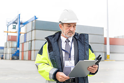Man with clipboard wearing safety jacket at container port - p300m1028786f by Milton Brown