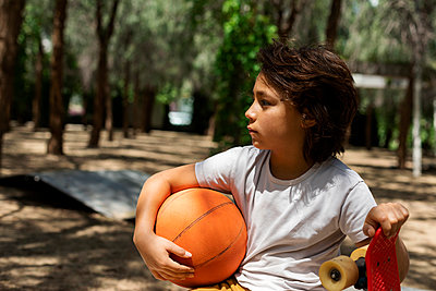 Thoughtful boy with basketball and skateboard in park - p300m2203139 by Valentina Barreto