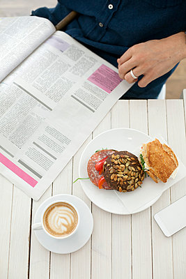 High angle view of young man reading magazine with coffee and breakfast on table at cafe - p426m927858f by Astrakan