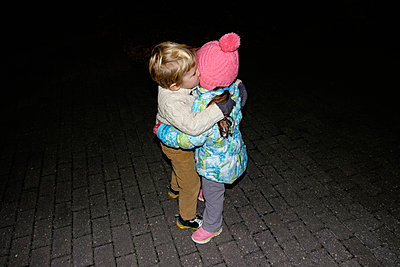 Boy ad girl hugging outdoors at night - p555m1232035 by Roberto Westbrook