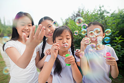 Chinese girls blowing bubbles in park - p555m1478589 by Jade photography