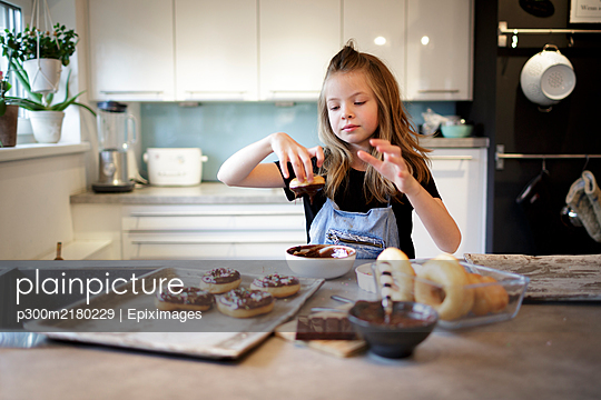 Portrait of smiling girl dipping home-baked doughnut into chocolate icing - p300m2180229 by Epiximages
