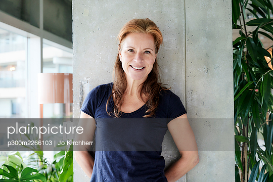 Mature woman with hands behind back standing against column in loft apartment at home - p300m2266103 by Jo Kirchherr