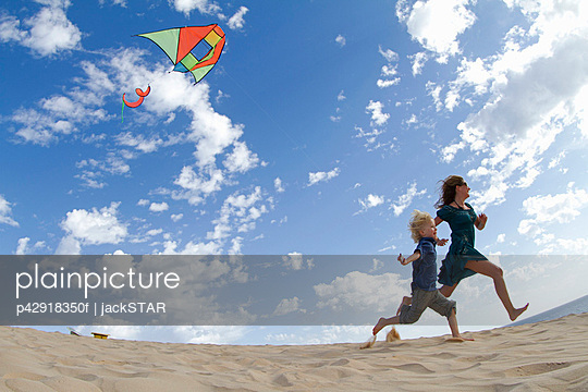 Mother and son flying kite on beach - p42918350f by jackSTAR