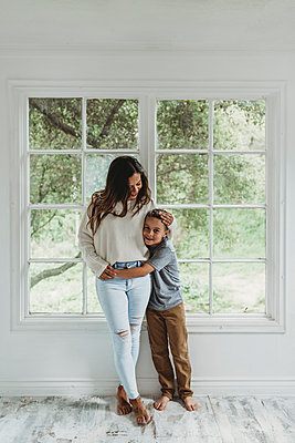 Full length view of mother and son hugging in studio - p1166m2130767 by Cavan Images