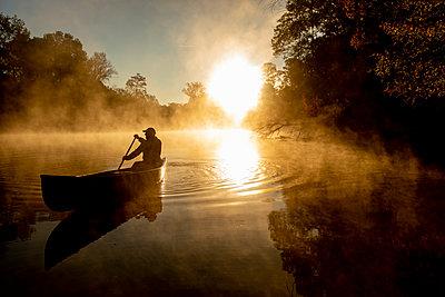Sunrise canoe ride on foggy river. - p1166m2269651 by Cavan Images
