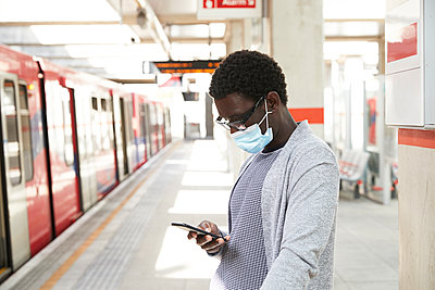 Male commuter wearing protective face mask while using mobile phone at railroad station - p300m2241029 von Pete Muller