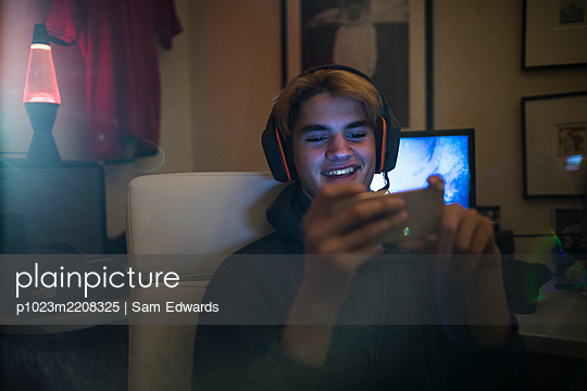 Smiling teenage boy with headphones using smart phone in bedroom - p1023m2208325 by Sam Edwards