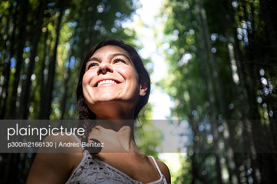 Japan, Tokyo, Low angle portrait of young woman standing in bamboo grove - p300m2166130 by Andrés Benitez