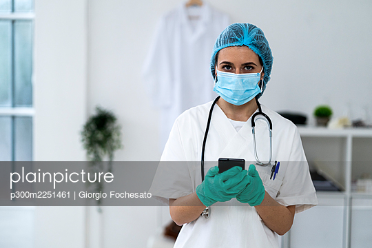 Young female doctor with surgical cap holding smart phone in clinic - p300m2251461 by Giorgio Fochesato