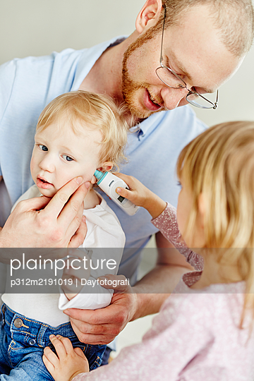 Girl measuring brothers temperature - p312m2191019 by Dayfotografi
