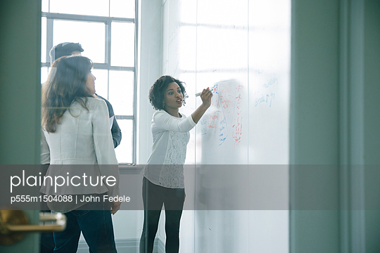 Businesswoman writing on whiteboard in meeting - p555m1504088 by John Fedele