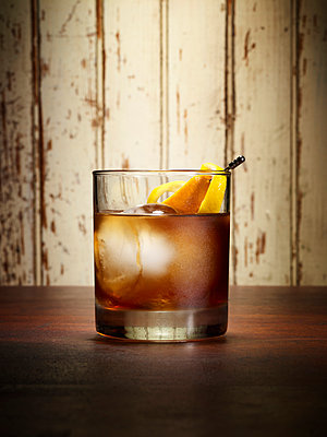 Whiskey with orange peel - p1166m1053920f by Gregory Miller