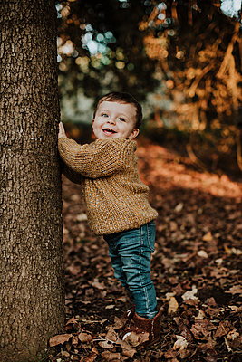 Cute toddler leaning on tree trunk in forest during sunset - p300m2252127 by Gala Martínez López