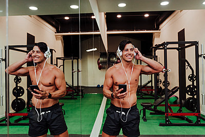 Smiling mid adult athlete adjusting headphones while standing by mirror in gym - p300m2273996 by Eva Blanco