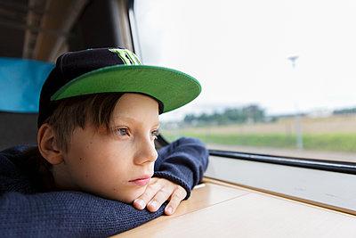 Boy in train looking through window - p312m1229262 by Susanne Kronholm