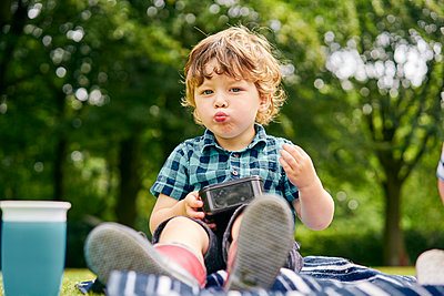 Toddler eating in park - p429m2164631 by GS Visuals