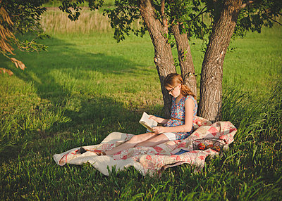 Caucasian girl reading book under tree in field - p555m1409705 by Shestock