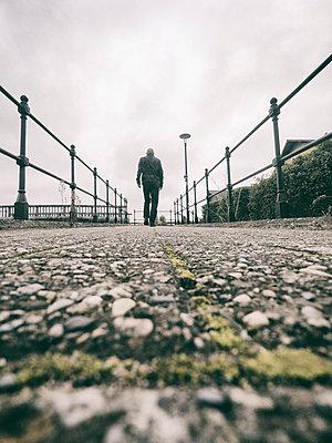 Rearview man walking between railings  - p597m2026533 by Tim Robinson