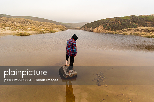 Person standing on log at edge of coastal inlet on foggy day at beach - p1166m2269364 by Cavan Images