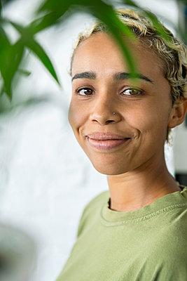 Frau blickt durch grüne Pflanze - p1156m1572810 von miep