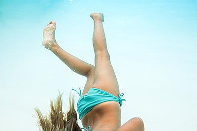 A girl in an aqua bikini swims underwater - p1166m2095755 by Cavan Images