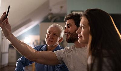 Happy young guy taking selfie with father and wife - p1166m2234827 by Cavan Images