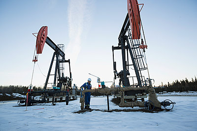Male worker working drilling rig snowy gas plant - p1192m1128005f by Hero Images