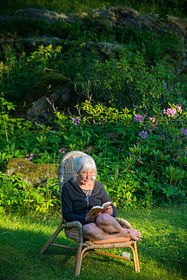 Woman reading book in garden - p1418m1592123 by Jan Håkan Dahlström