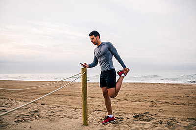 Sportive young man stretching on the beach - p300m1140789 by Bonninstudio