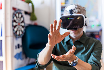 Portrait of mature man at home using Virtual Reality Glasses - p300m2030573 by Tom Chance