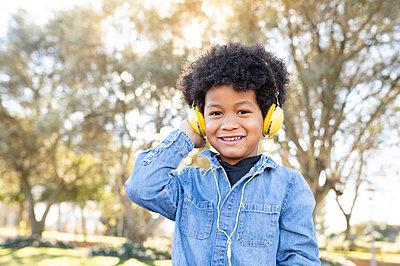 Boy listening music through headphones while sitting at park - p300m2252456 by Jose Carlos Ichiro