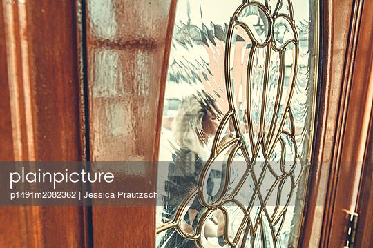 Blick durch Glastür auf eine junge Frau - p1491m2082362 von Jessica Prautzsch