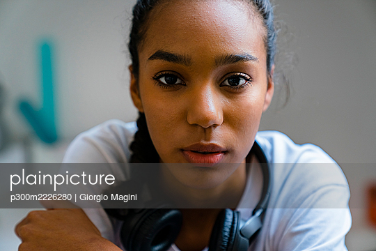 Close-up of teenage girl with headphone around neck sitting at home - p300m2226280 by Giorgio Magini