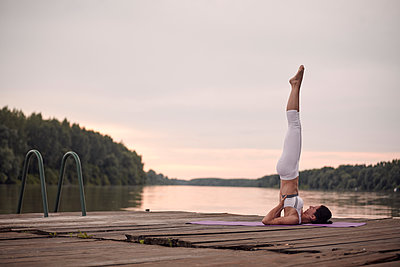 Woman practicing shoulder stand on pier by lake against cloudy sky during sunset - p1166m2011235 by Cavan Images