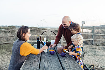 Cheerful family around picnic table drinking hot chocolate during fall - p1166m2095144 by Cavan Images