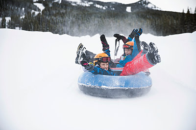 Playful brothers inner tubing in snow at tube park - p1192m1546615 by Hero Images