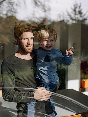 Father and son looking out of window at home - p300m2167239 by Kniel Synnatzschke