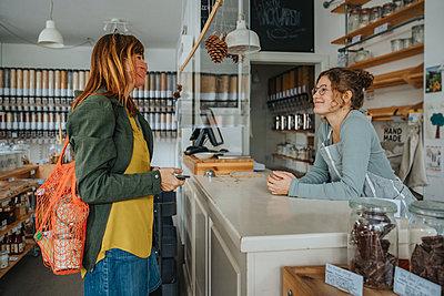 Customer chatting with store clerk in zero waste shop, Cologne, NRW, Germany - p300m2256204 von Mareen Fischinger