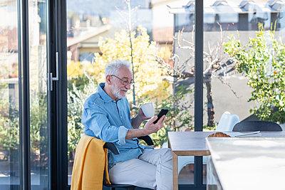Senior man using smart phone while having coffee at home - p300m2265890 by Emma Innocenti